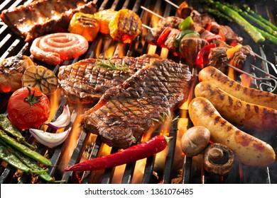 Verschiedenes köstliches Grillfleisch mit Gemüse, das über den Kohlen auf Grill schwebt