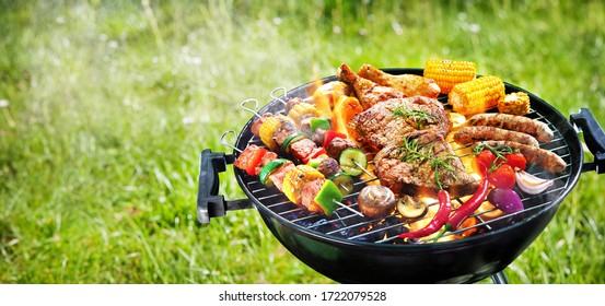 Sorgfältig gegrilltes Fleisch mit Gemüse auf Grillgrill mit Rauch und Flammen in grünem Gras