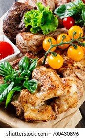 Assorted delicious grilled meat and vegetables with fresh salad and bbq sauce on cutting board on wooden background close up. Big set of Hot Meat Dishes. Top view