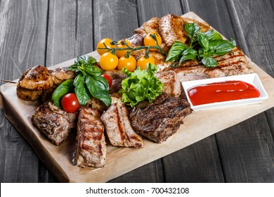 Assorted delicious grilled meat and vegetables with fresh salad and bbq sauce on cutting board on wooden background close up. Big set of Hot Meat Dishes
