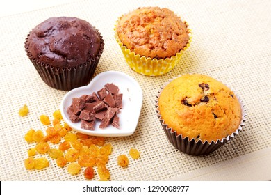 Assorted with Delicious homemade cupcakes with raisins and chocolate chips isolated on textile background. Muffins. Top view.