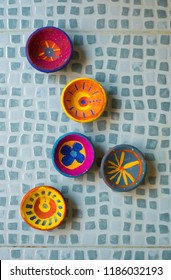 Assorted designs of hand-crafted traditional erthen lamps painted by kids for Diwali festival. Many Diwali clay lamps shot from above.
