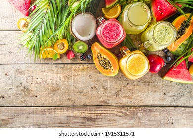 Assorted different fruit smoothies and juices with tropical fresh fruits and berries. Clean eating, healthy lifestyle, diet and vitamin drink beverages concept. Top view flatlay