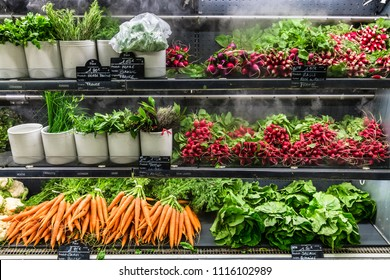 Assorted different kinds of fresh organic green vegetables on display in a French supermarket.  Background with radish; lettuce; carrot. Healthy vegetarian food concept. Paris, France