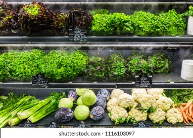 Assorted different kinds of fresh organic green vegetables on display in a French supermarket.  Background with cauliflower; cabbage; lettuce. Healthy vegetarian food concept. Paris, France