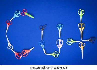 Assorted different pairs of household scissors arranged on a blue background to spell the word - Cut