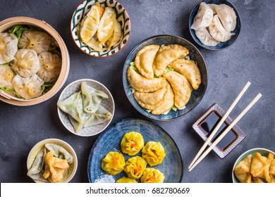 Assorted dim sum appetizers on rustic background. Set of Chinese food for share. Asian buffet. Traditional Chinese dim sum food. Top view. Different Chinese dumplings and snacks on table