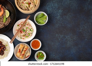Assorted dishes of traditional Chinese cuisine on red background: sweet and sour chicken with rice, dumplings, fried rolls, noodles and tea kettle. Asian food concept, top view, space for text