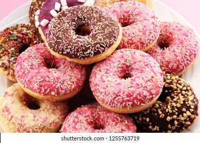 assorted donuts with chocolate frosted, pink glazed and sprinkles donuts.