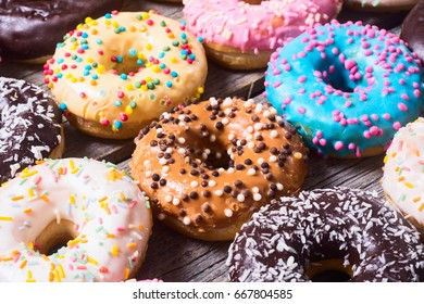 assorted donuts with chocolate frosted, pink glazed and sprinkles