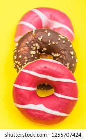 assorted donuts with chocolate on yellow background