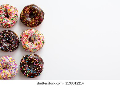 Assorted Donuts on white background, top down, layout, copy space, blank space. Chocolate and vanilla frosted doughnuts with colorful sprinkles. Glazed donuts with sprinkles white food background.