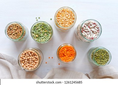 Assorted dried legumes and pulses in glass kitchen jars viewed from above with peas, lentils, beans, chickpeas, on a white cloth