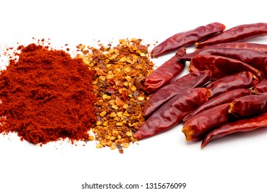 Assorted dried red chili pepper, red paprika and crushed red chili over white background