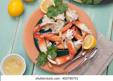 Assorted Dungeness crab legs with butter mustard sauce and fresh lemons.