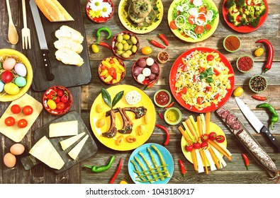Assorted Easter food on wooden background flat lay top view - Italian rustic kitchen table with pasta , lamb ribs , variety of colorful side dishes  ready to eat - Culinary concept of spring holidays