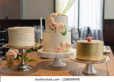 Assorted Elegant Wedding Cake Trio. One wedding cake decorated with butter cream ruffles, one decorated with gold, and a two tier with edible butter cream roses.