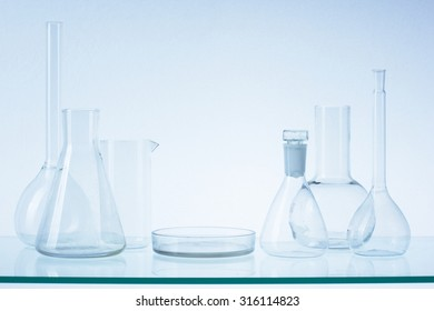 Assorted empty laboratory glassware, test-tubes. Blue tone medical background. Copy space