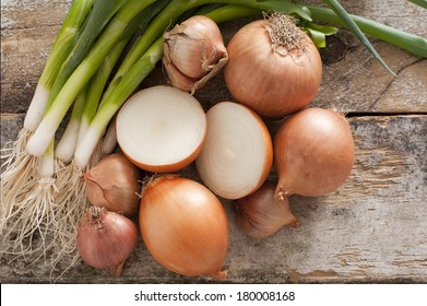 Assorted farm fresh onions on a rustic wooden table with spring onions, brown onions and shallots , with one onion cut in half in the centre of the arrangement, overhead view