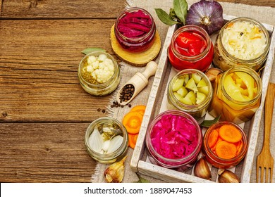 Assorted of fermented vegetables in glass jars. Preserved season vegetables concept, probiotics food for healthy lifestyle. Vintage wooden table, top view