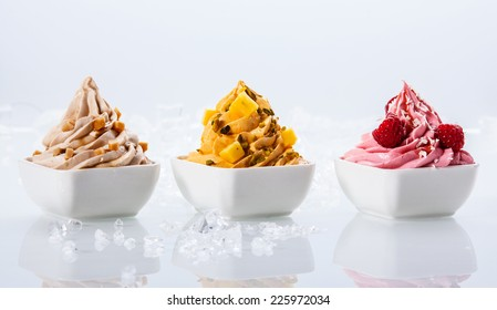 Assorted Flavor Delicious Frozen Yogurts on Small White Bowls Isolated on White Background