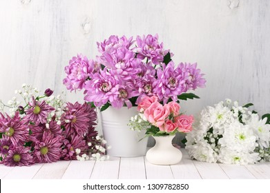 Assorted flowers on white wood table against rustic shabby wall.