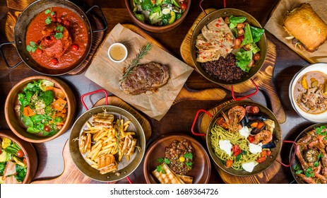 Assorted food set on table, Pasta with seafood, steak ribeye, club sandwich, turkey with black rice, salad with kinoa, tartar from beef, fried loungustine