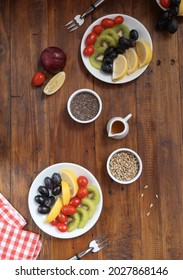Assorted fresh cut fruit.  Served on a wooden table as a healthy breakfast menu.  Kiwi, grapes, lemon and cherry tomatoes. Comes with honey, sunflower seeds and chiaseed for pouring.