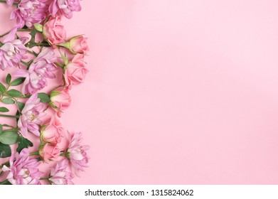 Assorted fresh flowers border on pink background. Top view point.