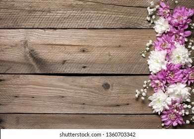 Assorted fresh flowers composition as border on rustic old wooden background. Top view point.