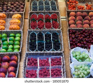 Assorted fresh fruit on display at a farmers market or in a supermarket including berries, peaches, dragon fruit, grapes, cherries and limes