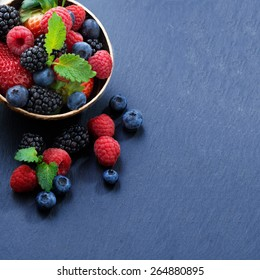 Assorted fresh garden berries on a black background, space for text, close-up