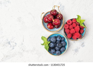 Assorted fresh juicy berries. Cherry, blueberry and raspberry in bowls, top view