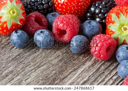 assorted fresh juicy berries on wooden background, horizontal, close-up