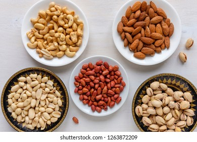 Assorted fresh nuts in bowls with groundnuts, peanuts, cashews, almonds and pistachios viewed from above on a white table in a healthy diet concept