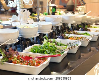 Assorted fresh salads displayed on a buffet in individual containers at a catered event or celebration, receding perspective