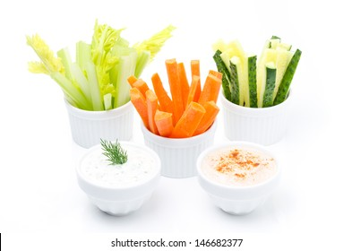 Assorted fresh vegetables (celery, cucumber and carrot) and two yogurt sauce isolated on a white background