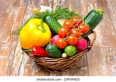 assorted fresh vegetables and herbs in a wicker basket on a wooden background close-up