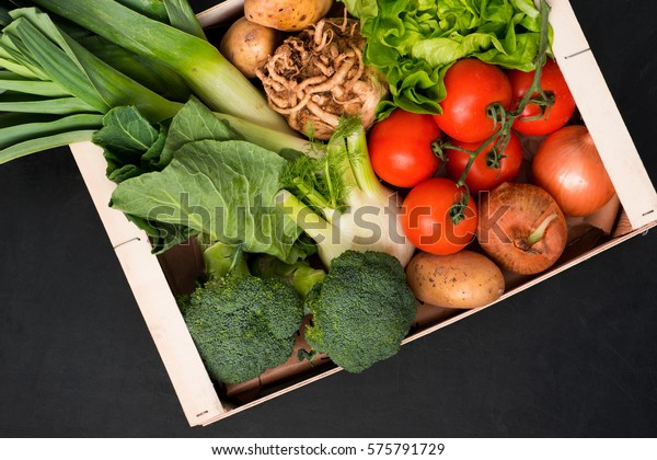 Assorted fresh vegetables including, tomatoes, fennel, potatoes, onions, broccoli, leeks, celeriac, and salad greens in a wooden box.