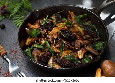Assorted fried mushrooms (chanterelles, baby bella mushrooms, morels and shiitake) with herbs and aleppo pepper in the old frying pan