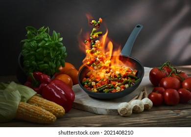 Assorted fried vegetables in a pan with a flame of fire. Flambe vegetables on a wok frying pan flying in the air. Concept of restaurant menu, cooking, Asian food.