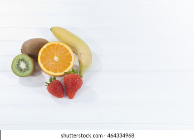 Assorted fruit on white wooden background with space for text