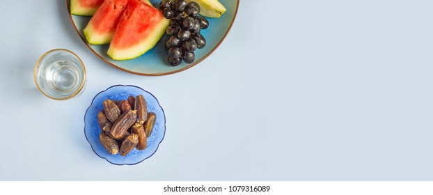 An assorted fruit platter along with sweet dates served with glass of drinking water. A healthy and nutritious food to break an Iftar fast during holy month of Ramadan.