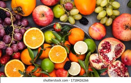 Obstsorte. Verschiedene Früchte auf grauem Hintergrund, die gesamte Oberfläche ist mit Zitrusfrüchten, Granatapfeln, Äpfeln, Trauben, Erdbeeren bedeckt. Draufsicht