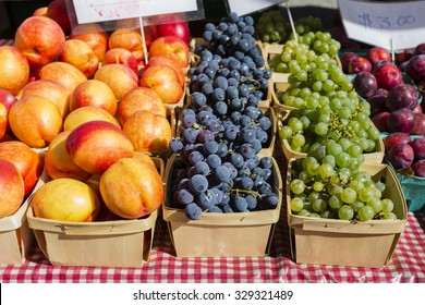 Assorted fruits (plums, grapes and peaches) in baskets for sale on a table with a red checkered picnic table cloth.
