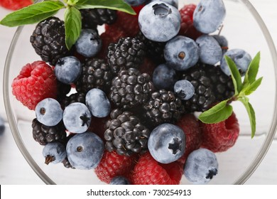 Assorted garden and wild berries. Mix of fresh organic strawberries, raspberries, blueberries and blackberries in glass bowl on white wood, top view, closeup
