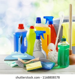 Assorted generic cleaning supplies in plastic bottles and sprayers with scrubbing and toilet brushes, a plunger and bucket in a square format