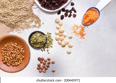 Assorted grains, dried raisins, hazel and macadamia nuts displayed on a white surface for a healthy vegetarian diet or cooking ingredients, overhead view with copy space