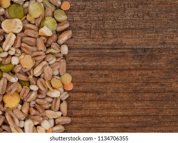 Assorted grains and pulses mix on wooden background, with copy space. Winter food includes split peas, red and yellow lentils, pearl barley, kamut, spelt.