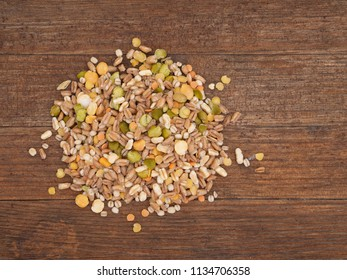 Assorted grains and pulses mix on rustic wood board, overhead view. Winter food includes split peas, red and yellow lentils, pearl barley, kamut, spelt.